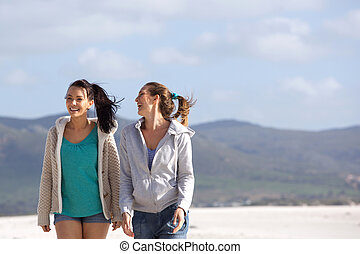 Two friends walking on the beach smiling