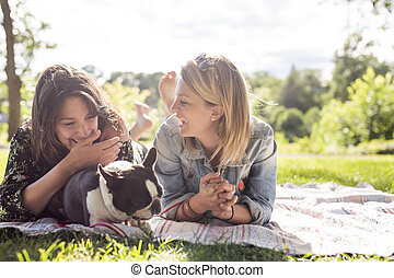 Two friends woman with terrier dog outside at the park