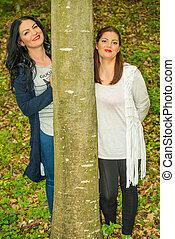 Two friends women behind tree