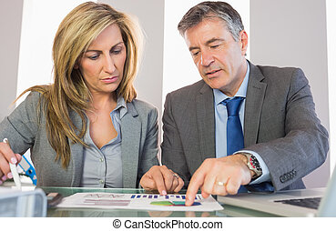 Two frowning business people pointing at a graphic