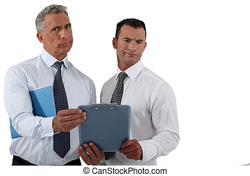 Two frowning businessmen holding clip-board