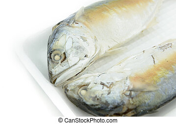 Two frozen steamed mackerel on foam container