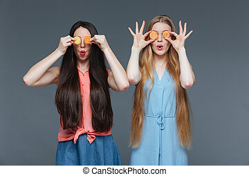 Two funny amazed women covered their eyes with marmalade ...