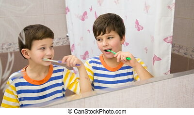 Two funny brothers cleaning his teeth together in the...