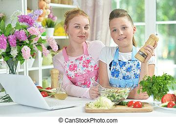 Two funny girls preparing fresh salad