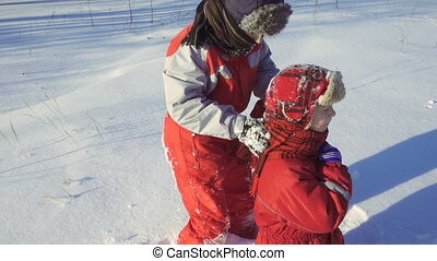 Two funny kids playing together at snow on winter park,...