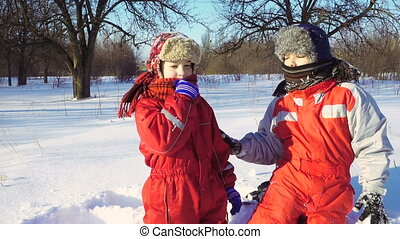 Two funny kids playing together at snow
