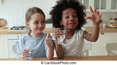 Two funny mixed race children drinking water showing thumbs ...