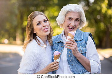 Two funny women eating ice cream