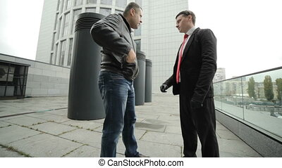 Two gangster men met to hand over a gun to order a murder.