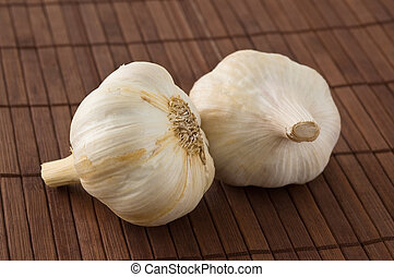 Two garlic heads on a bamboo mat. - Two garlic heads on a...