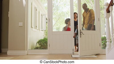 Two generation family entering their house