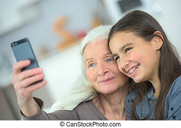 two generation women making a funny selfie together