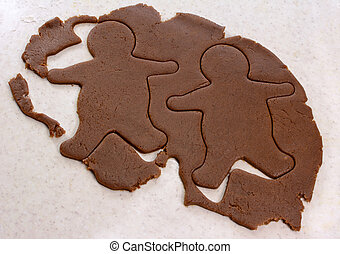 Two gingerbread men in cookie dough