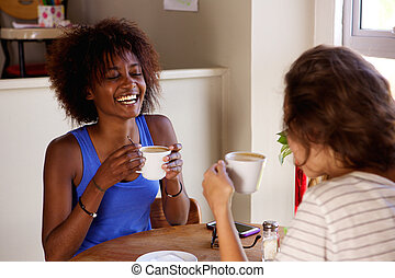 Two girl friends enjoying a cup of coffee at cafe