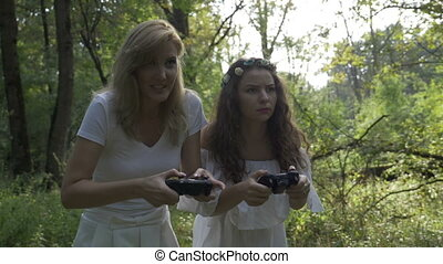 Two girl friends holding joystick game controllers in hands...