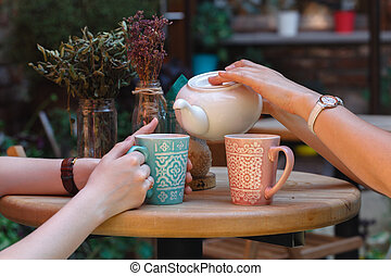Two girl-friends talk and drink tea in cafe, outdoors