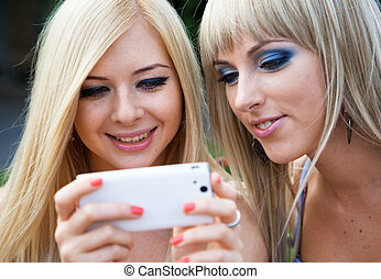 Two girl friends using a smartphone