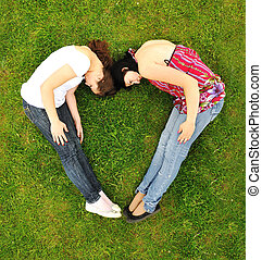 Two girl making a shape of heart