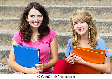 Two girl students at school smiling