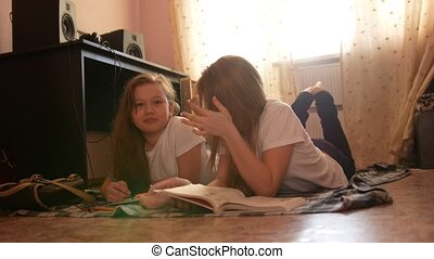 Two girl teens reading a book and drawing while lying on the floor at home