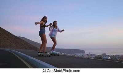 Two girlfriend girls in shorts and sneakers ride skateboards...