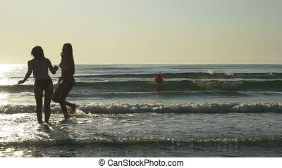 Two girlfriends dancing, and playing in the sea water