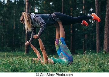 Two girlfriends doing partner yoga pose, flying warrior, on...
