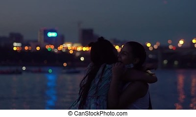 two girlfriends embrace on a background of a night city. slow motion
