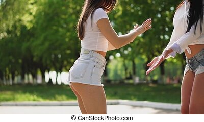 Two girlfriends in short denim shorts and white t-shirts are...