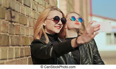 Two girlfriends in sunglasses and stylish leather jackets take a photo from a mobile phone near a brick wall on the street. Do selfie.