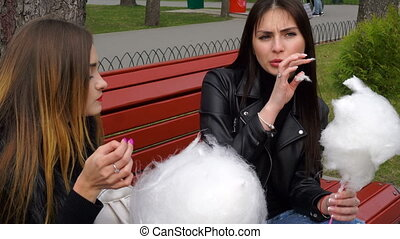 two girlfriends in the park eating cotton candy and talk