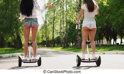Two girlfriends riding on white Segways launch soap bubbles.
