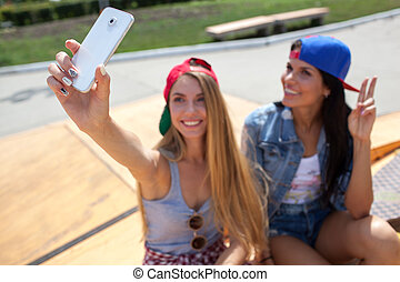 girlfriends taking a selfie photo on the skate park