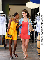 Two girlfriends walking and talking at shopping mall