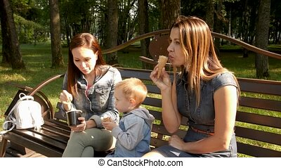Two girlfriends with a child sit on a bench in the city Park and eat ice cream. Homosexual couple, young lesbian women. A walk in the city Park.