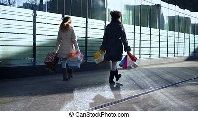 Two girlfriends with bags in their hands are walking down street