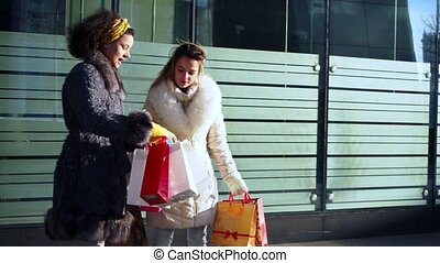 Two girlfriends with packages in their hands are discussing purchases
