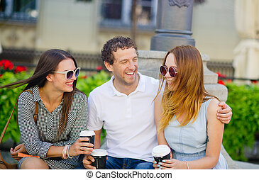 Two girls and a guy are drinking coffee and talking lively.