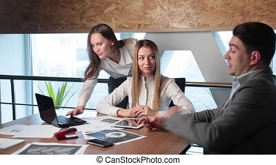 Two girls and a man in the office working