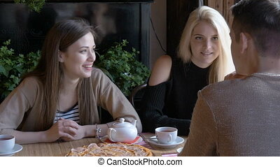 Two girls and a young man talking in a cafe sitting at a table. They drink tea and eat pizza. They tell the news, they smile. Close-up