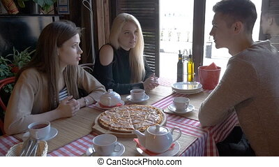Two girls and a young man talking in a cafe sitting at a table. They drink tea and eat pizza. They tell the news, they smile.