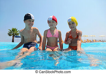 Two girls and boy sit on skirting in  pool and speak, underwater package shot