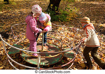 Two girls and one boy play on roundabout in autumnal park