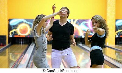 Two girls and one guy dance inside bowling club, they draw...