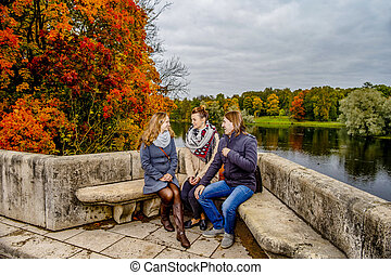 Two girls and one guy on a bench