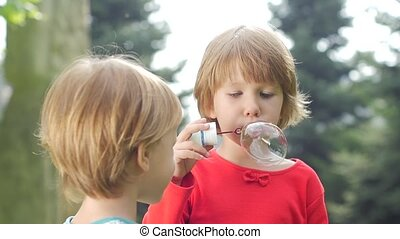 Two girls are blowing bubbles in the park, Slow motion. Close up