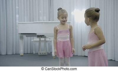 Two girls are having fun in ballet studio indoor. They talk friendly and turn bodies, raising their hands up. Adorable children dressed in classical dance clothes spend good time, learn basics of classical choreography, which positively influences inner world of kids, makes them harmonious and ...