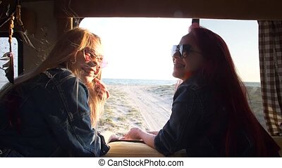 two girls are laughing against the background of the autotrailer behind which the seashore