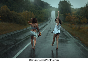 Two girls are on the roadway in the rain.